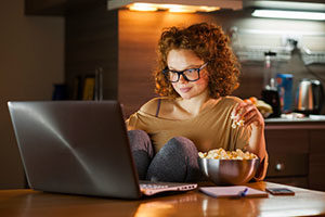 girl eating popcorn while using laptop