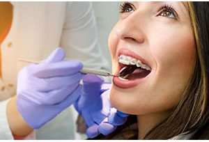 woman getting her braces examined