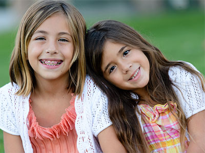 young girl with braces smiling with younger sister